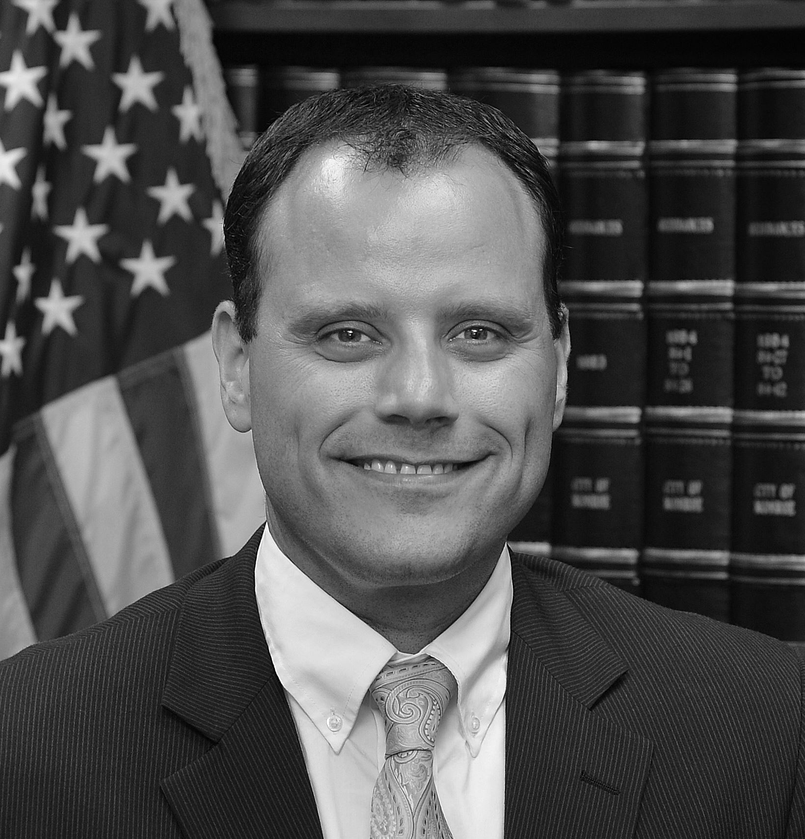 Black and white headshot of a man in a suit against a background of legal books and the flag